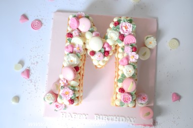 "Letter ""M"" with buttercream, macarons and berries"