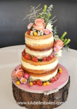 2 Tier naked cake layered with strawberry jam and vanilla bean buttercream, decorated with fresh flowers & berries