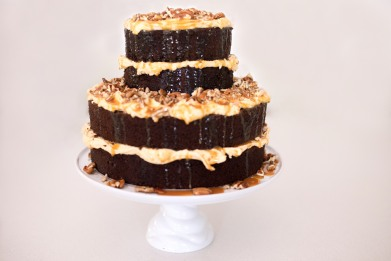 Chocolate naked cake with caramel buttercream filling topped with crushed pecan nuts and drizzled with toffee sauce