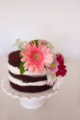 Red velvet naked sponge cake decorated with fresh flowers
