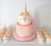 2 tier sprinkle unicorn cake and cupcakes